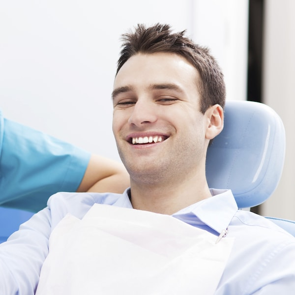Young man sitting in a blue dental treatment chair and smiling with his restorative dentist