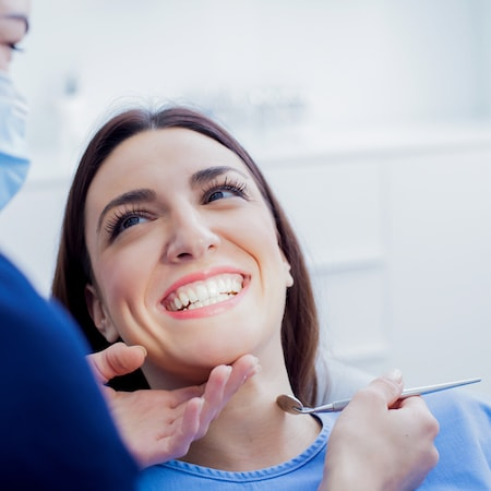A close up of a family dentist holding up a dental mirror to a female patient