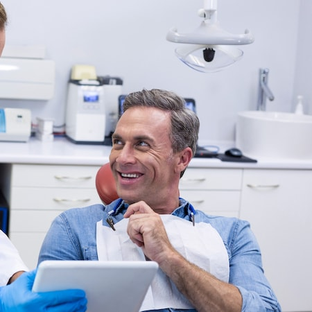 A man talking to the family dentist to his right while smiling