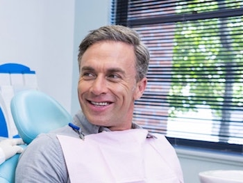 Mature man sitting in a dental chair discussing dental services with the dentist to his right