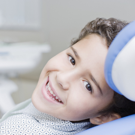 Young boy laying a in dental chair and looking back while smiling