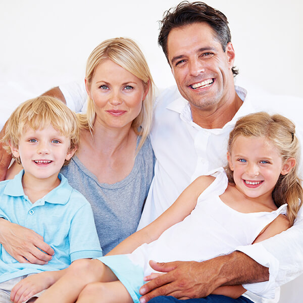 A family of four smiling while they are sitting on a sofa and enjoying our difference