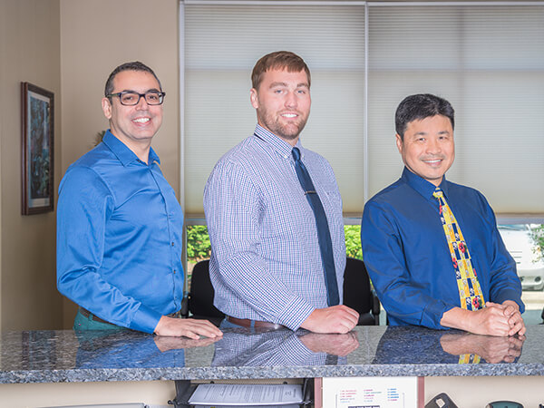 Our dentists in Graham, WA leaning on the front desk of the office