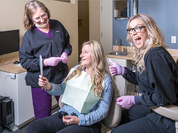 Your Graham dentist and hygienist smiling with a patient while she looks in a handheld mirror