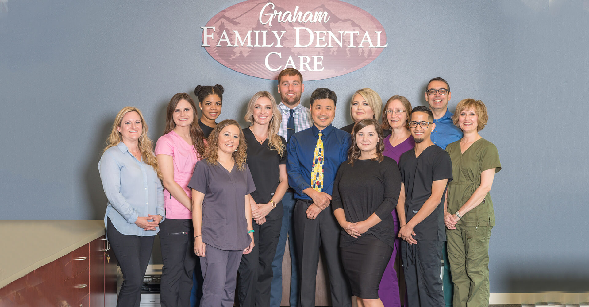 The entire Graham Family Dental Care team standing together under our logo in the office